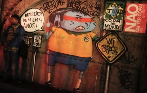 A man stands next to graffiti referring to the 2014 World Cup in Sao Paulo