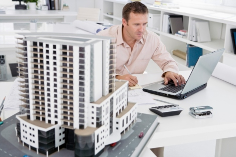 Man using laptop next to scale model